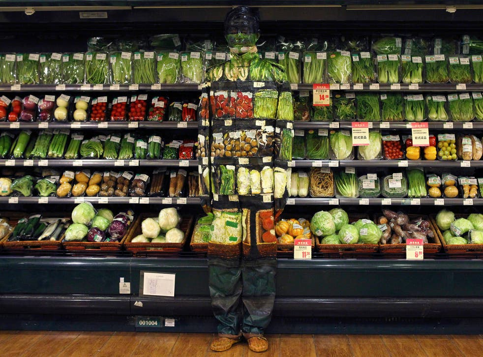 Artist Liu Bolin, also known as the 'Vanishing Artist,'  demonstrates an art installation by blending in with vegetables displayed on the shelves at a supermarket in Beijing.