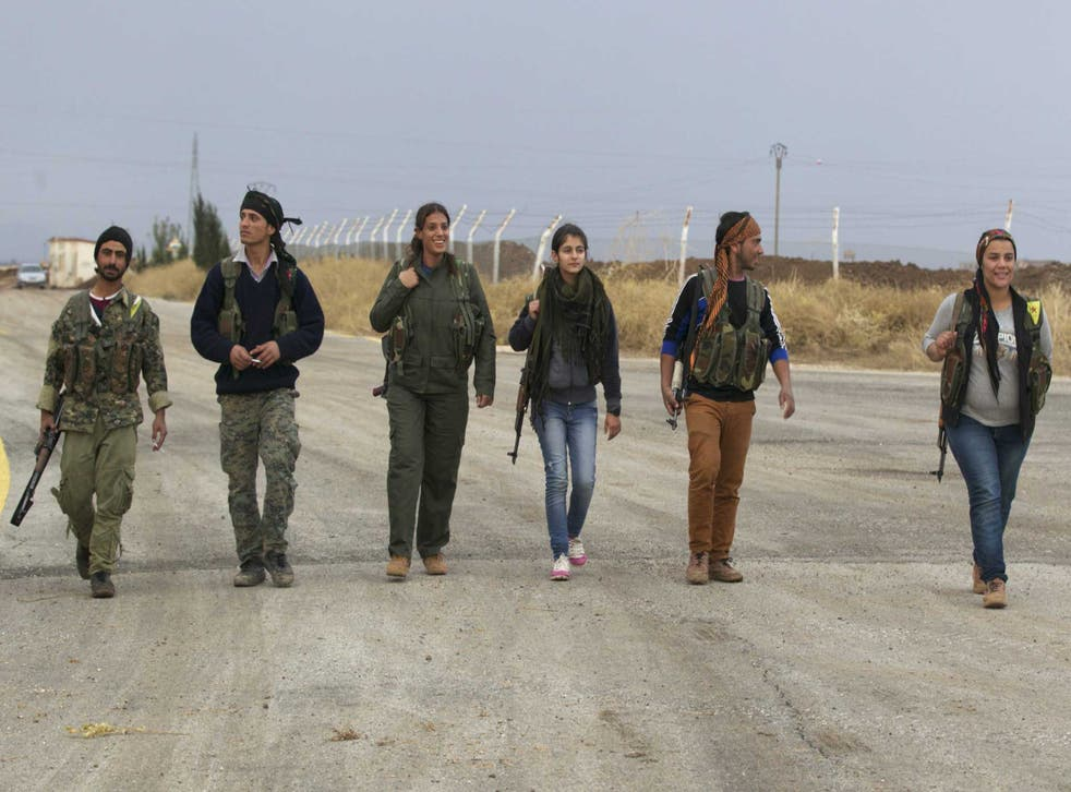 Members of the Kurdish People's Protection Units walk together in Al-Rmelan, Qamshli province