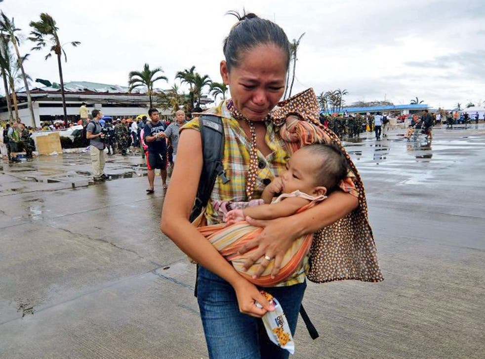 A woman weeps as she carries a child to a military aircraft to evacuate the area which has been devastated by Typhoon Haiyan