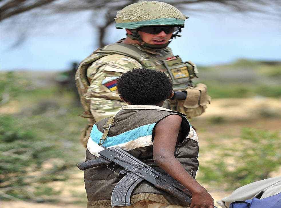 A young Somali boy with an AK-47 rifle talks to a British soldier in July 2012