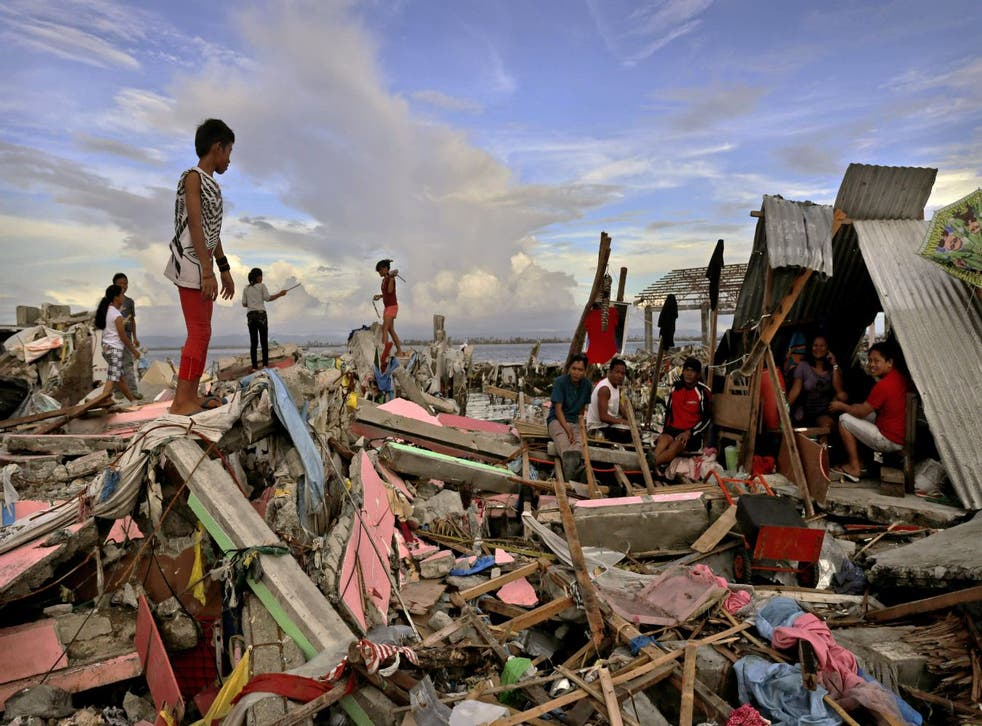 Residents gather amongst the devastation in the aftermath of Typhoon Haiyan in Tacloban, Leyte, Philippines.