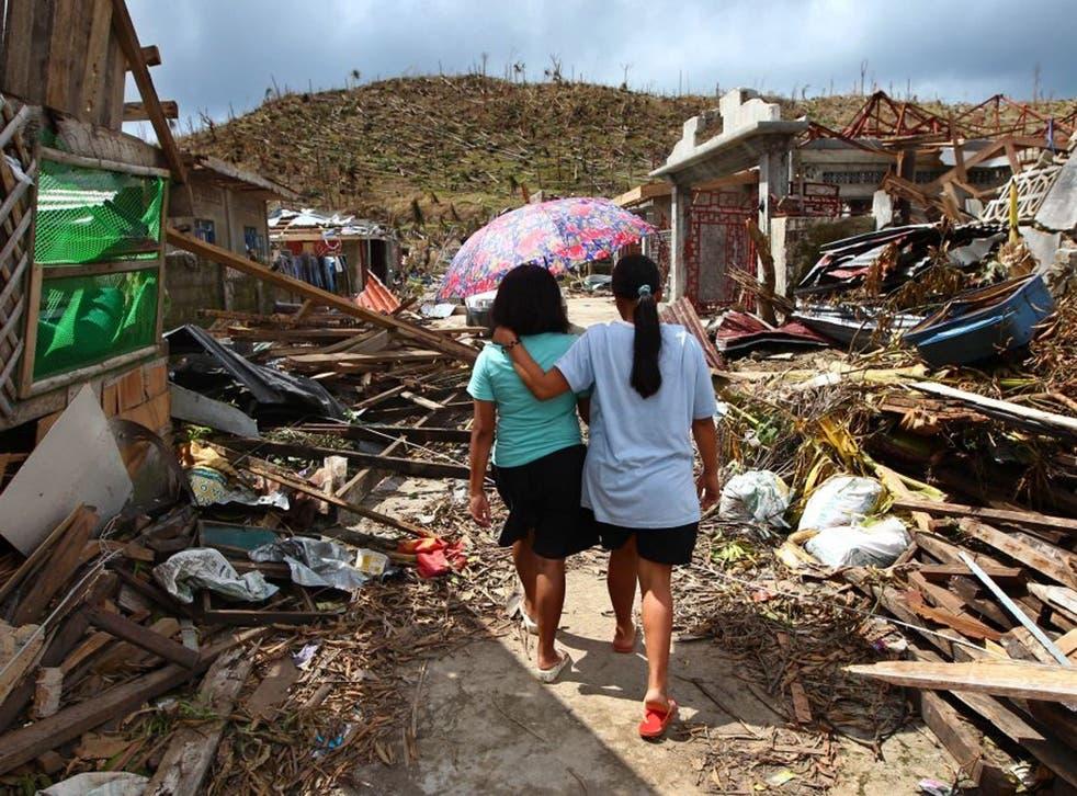 Typhoon Haiyan survivors walk amid ruins of buildings in Maraboth, Philippines