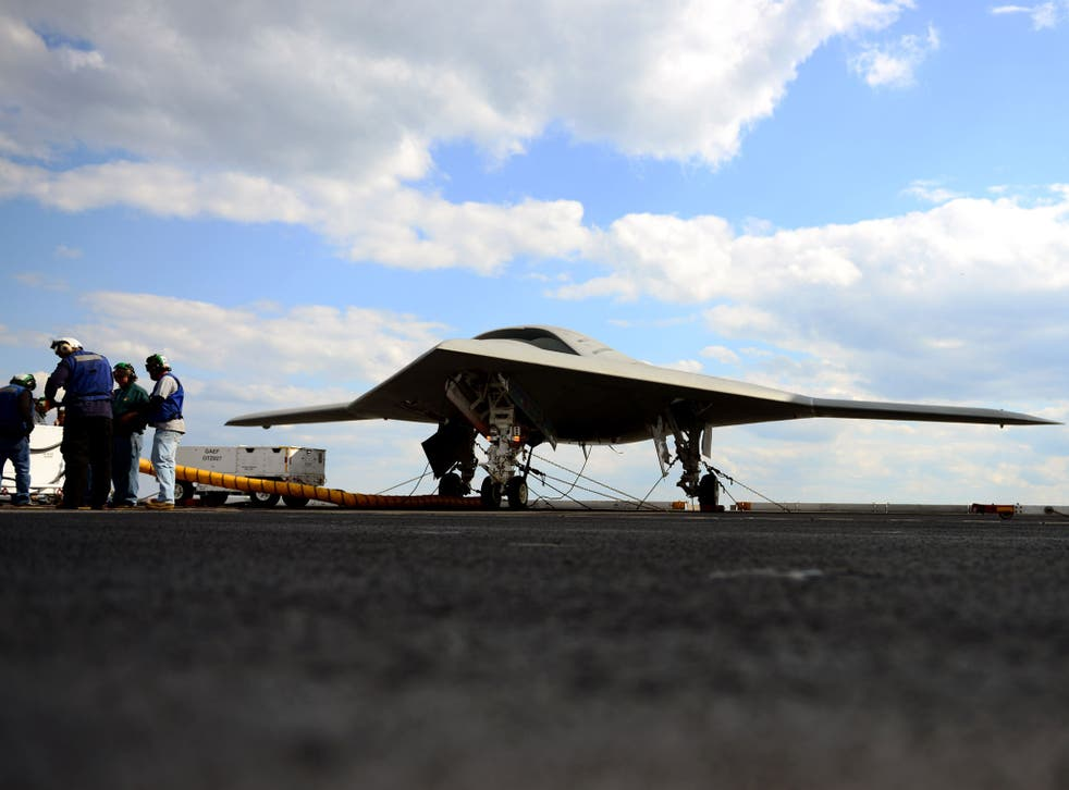 Northrop Grumman personnel conduct pre-operational tests on an X-47B Unmanned Combat Air System (UCAS) demonstrator on the flight deck of the aircraft carrier USS George H.W. Bush