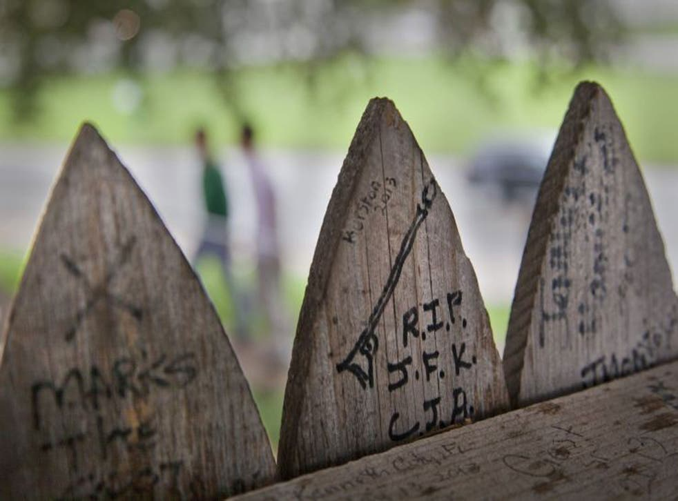 RIP JFK: the stockade fence that surrounds the Grassy Knoll is covered with messages and drawings left there by visitors
