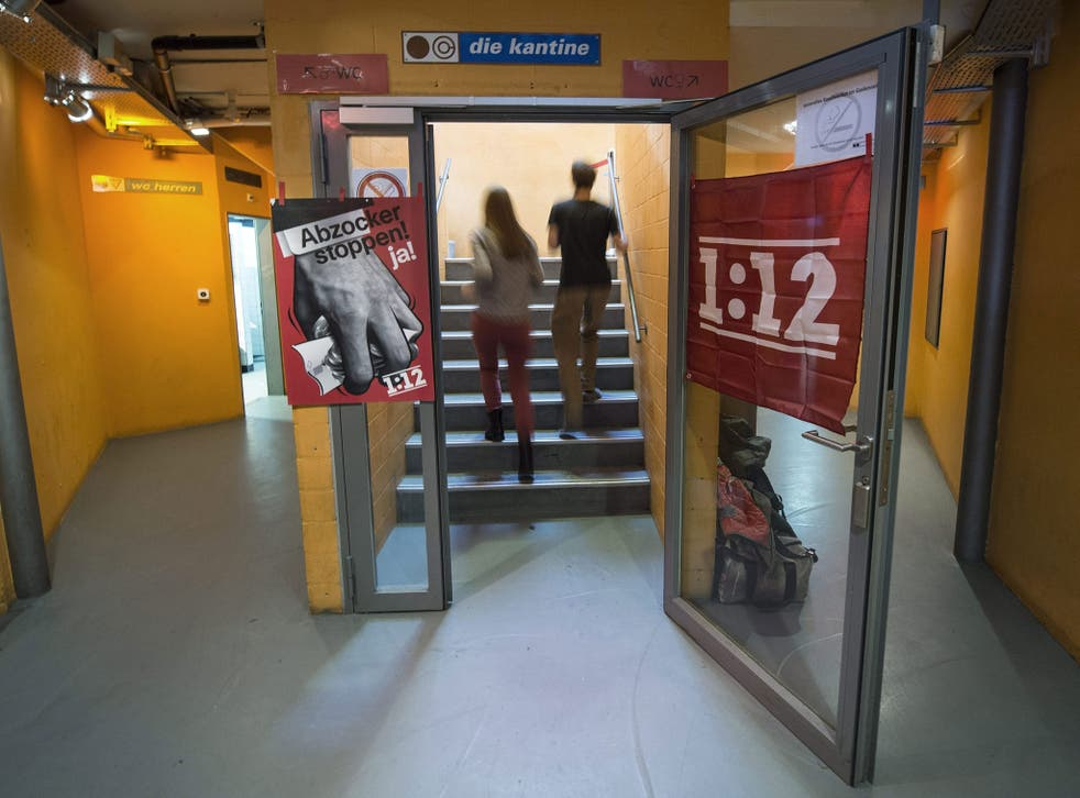 A poster reading '1:12' (R) hangs next to a poster with a slogan in German reading: 'Stop con atists - yes!'