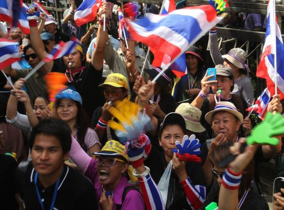 Anti-government protesters blow whistles and wave national flags as they gather outside the Industry Ministry in Bangkok