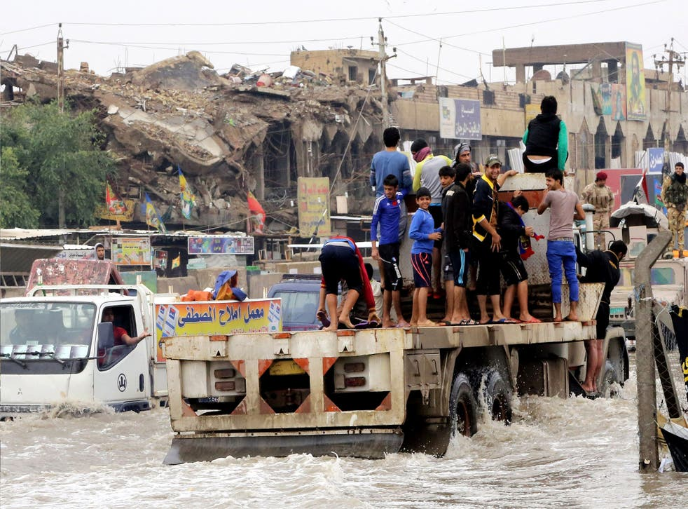 Iraqis make their way through the flooded streets of Baghdad after last week's storm. Many people have criticised the response from central and provincial authorities