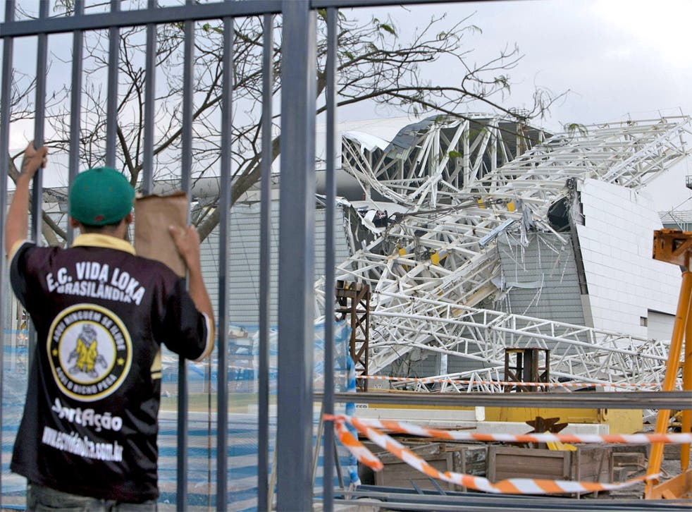 A fan inspects the damage at the partly finished Arena Corinthians in Sao Paulo, where two people died in an accident