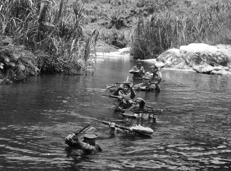 1957: Soldiers on patrol holding their guns above their heads as they wade up a river in the jungle during the Malayan Emergency