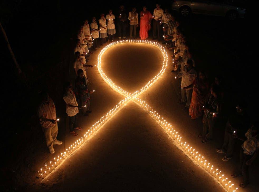 Nursing students and medical staff hold candles and stand by a formation in the shape of a red ribbon, the universal symbol of awareness and support for those living with HIV, made with candles