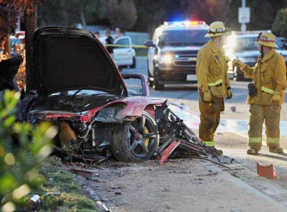 Sheriff's deputies work near the wreckage of a Porsche that crashed into a light pole