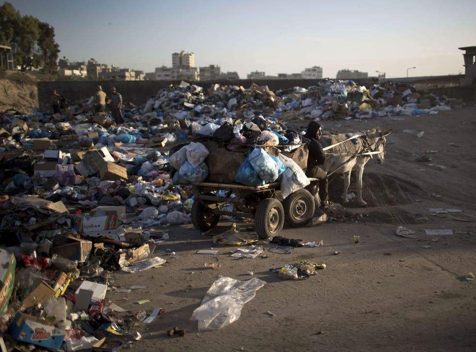 Palestinian workers in Gaza City use a donkey cart to collect the piles of rubbish due to the severe fuel shortage