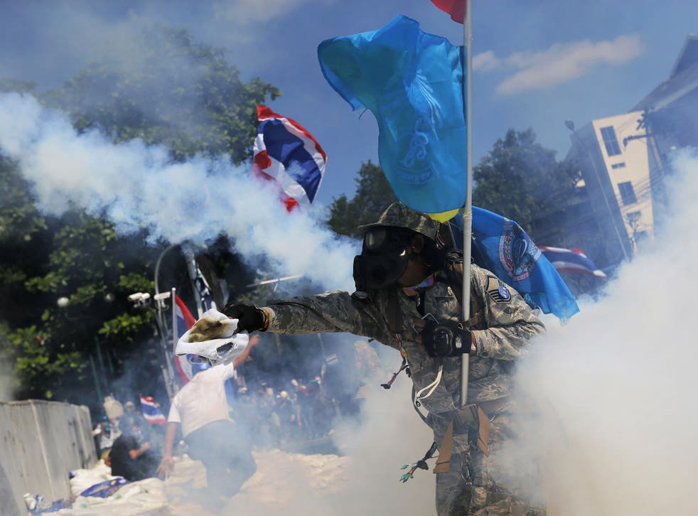 A protester throws back a tear-gas canister during clashes with police near Government House in Bangkok