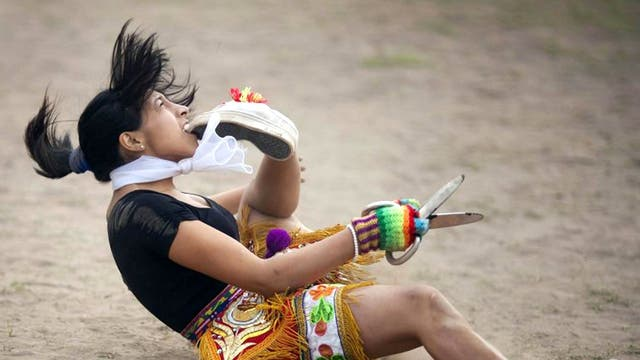 A 'scissors' dancer grabs her shoe with her mouth while performing in a national scissors dance competition in the outskirts of Lima, Peru