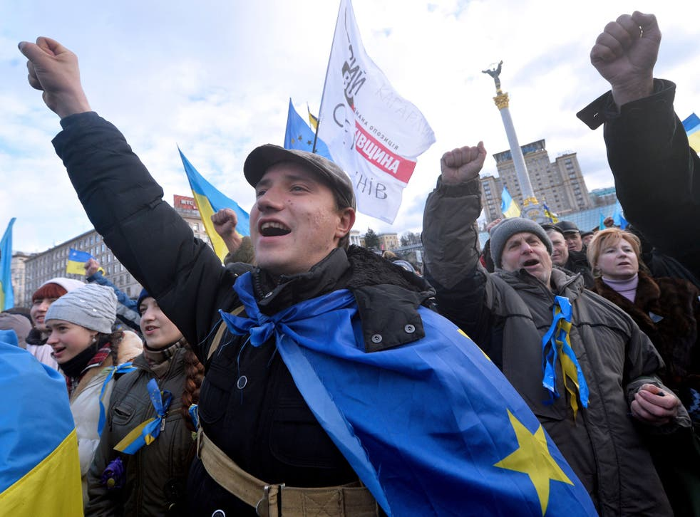 People shout slogans and wave flags of Ukraine and the European Union during a rally of the opposition on Independence Square in Kiev