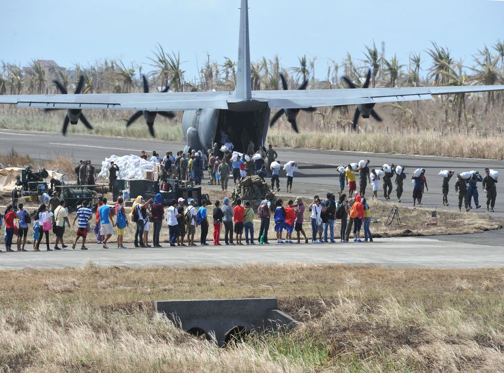 A crowd gathers on the airstrip in Guiuan as a US plane delivers aid in the aftermath of Typhoon Haiyan