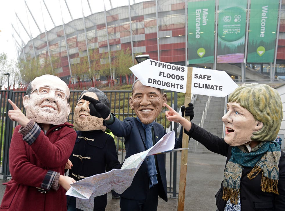 Activists wearing masks featuring France's President Francois Hollande, Japanese Prime Minister Shinzo Abe,United States President Barack Obama and Germany's Chancellor Angela Merkel discuss which climat option to take in front of the National Stadium hos