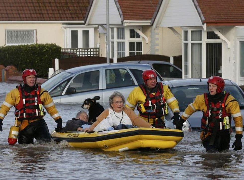 After the deluge: Residents are evacuated by inflatable boat, in Rhyl, north Wales