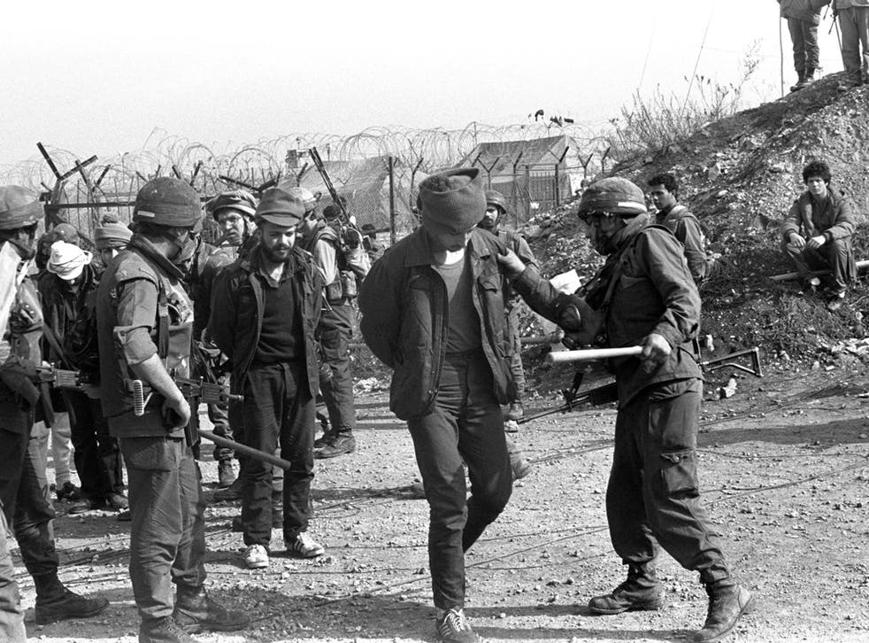 In this archive image provided by the Israeli Government Press Office (GPO), during Israel's Lebanese war, Israeli soldiers check the identity of Lebanese prisoners before they leave an Israeli military prison on their release from Ansar detention camp Ap