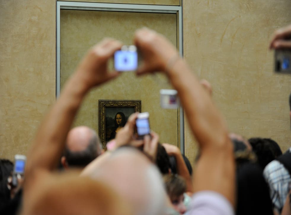 Tourists take souvenir photos of Italian painter Leonardo da Vinci's famed portrait Mona Lisa at the Louvre Museum in Paris.