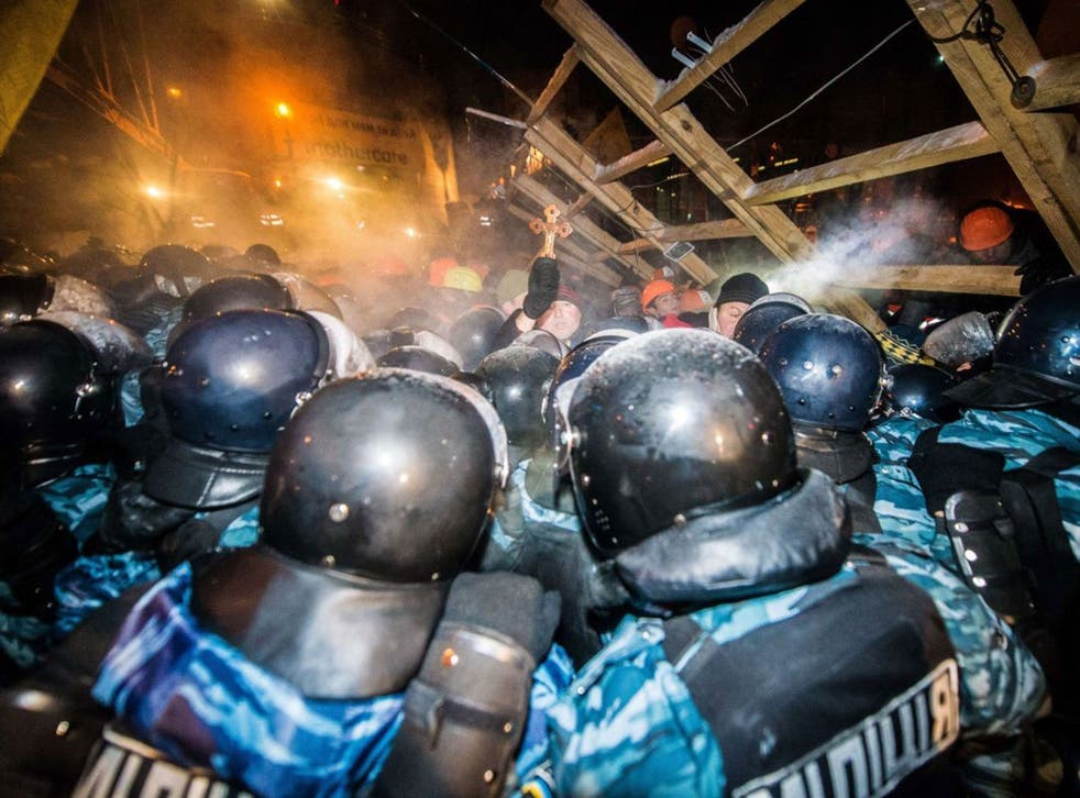 Riot police assault a  barricade held by protesters on Independence Square in Kiev late on 11 December, 2013