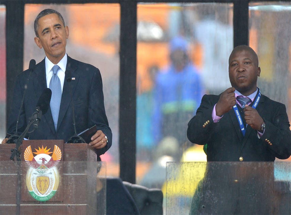 Obama delivers his speech next to a sign language interpreter, who has been accused of being a fake