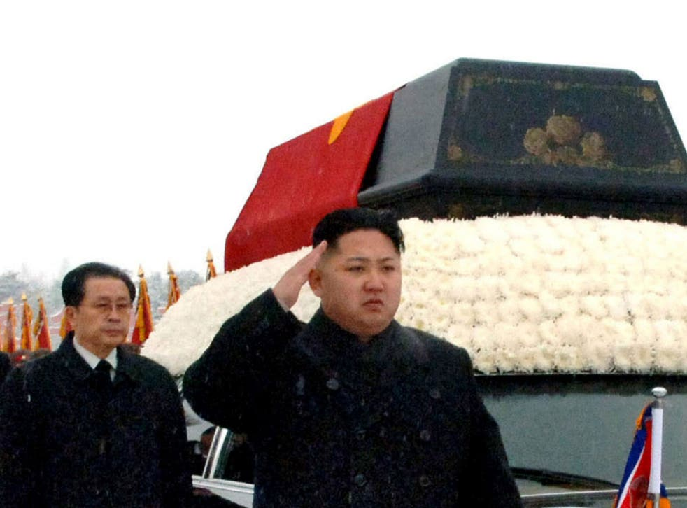 North Korea's Kim Jong Un, front, salutes beside the hearse carrying the body of his late father and then North Korean leader Kim Jong Il during the funeral procession in Pyongyang, North Korea as Jang Song Thaek follows
