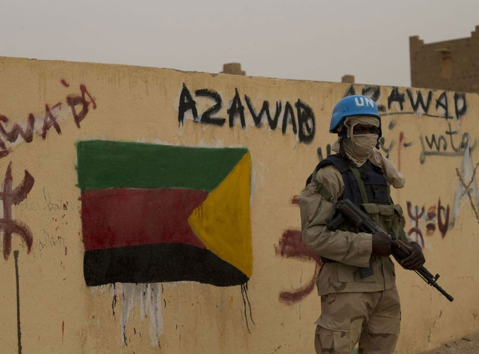In this Sunday, July, 28, 2013 file photo, a United Nations peacekeeper stands guard at the entrance to a polling station covered in separatist flags and graffiti supporting the creation of the independent state of Azawad, in Kidal, Mali. A bomb explosio