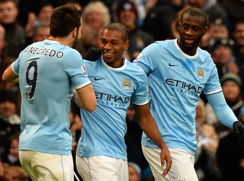 Fernandinho (C) celebrates with Alvaro Negredo (L) and Yaya Toure (R) after scoring against Arsenal