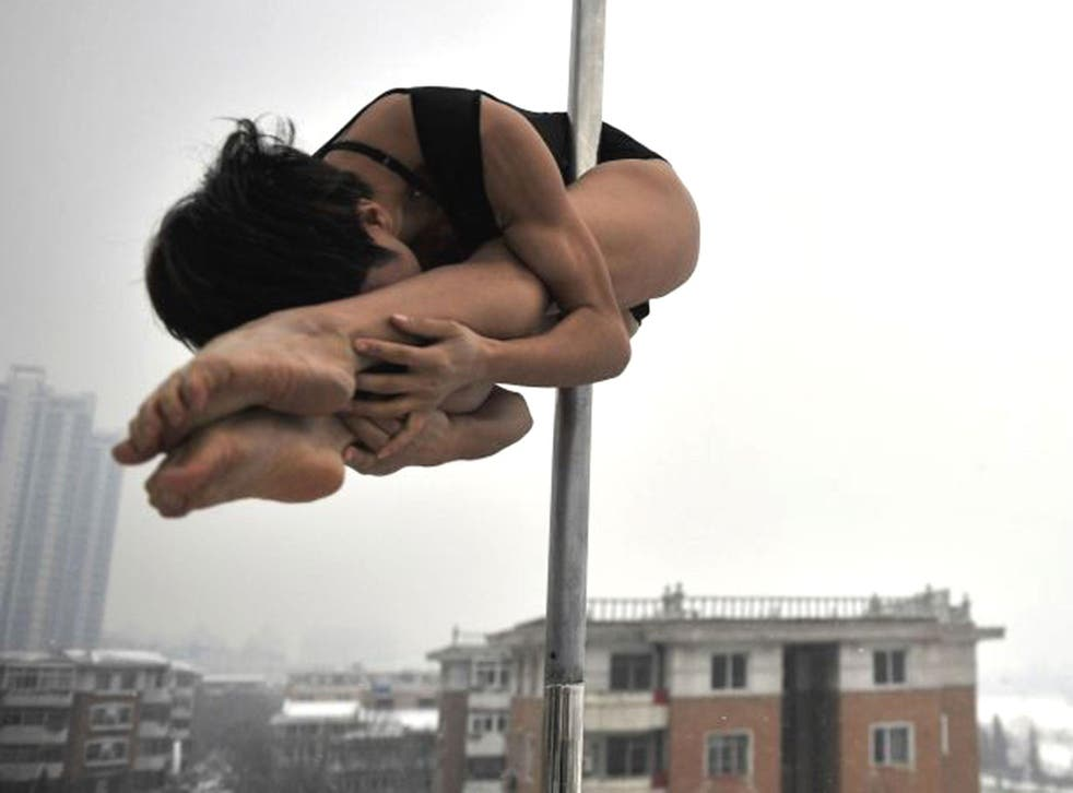 A pole dancer practices during a promotional event by members of China's national pole dancing team