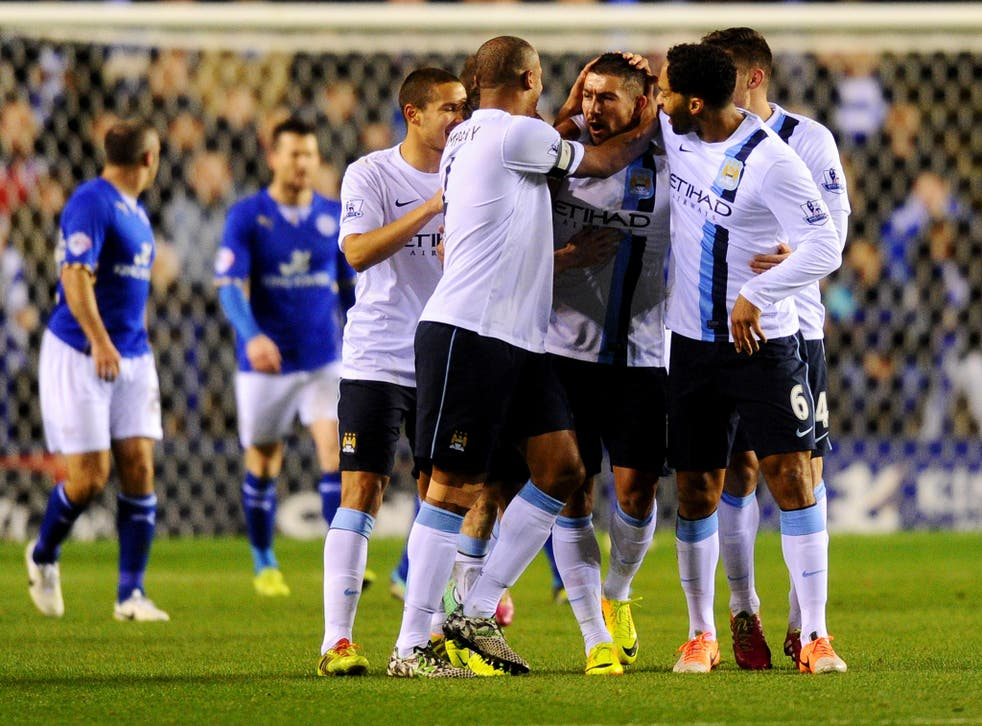 Aleksandar Kolarov of Manchester City (2R) celebrates with team mates as he scores their first goal during the Capital One Cup against Leicester