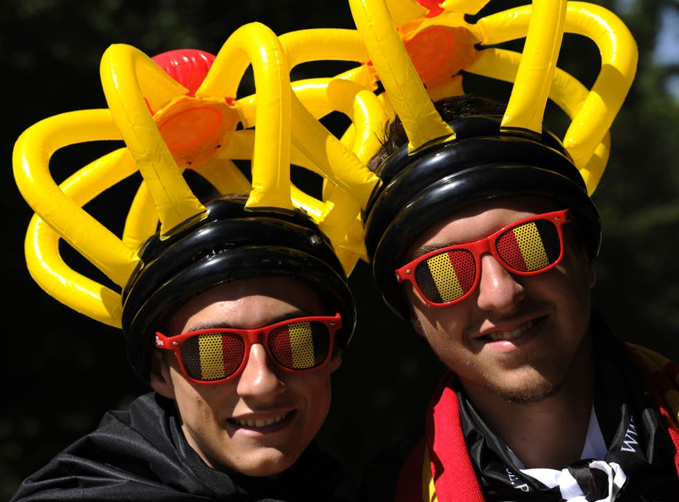 File: A pair of Belgians wearing glasses and hats in the colours of the Belgian flag pose on Belgian National day on 21 July
