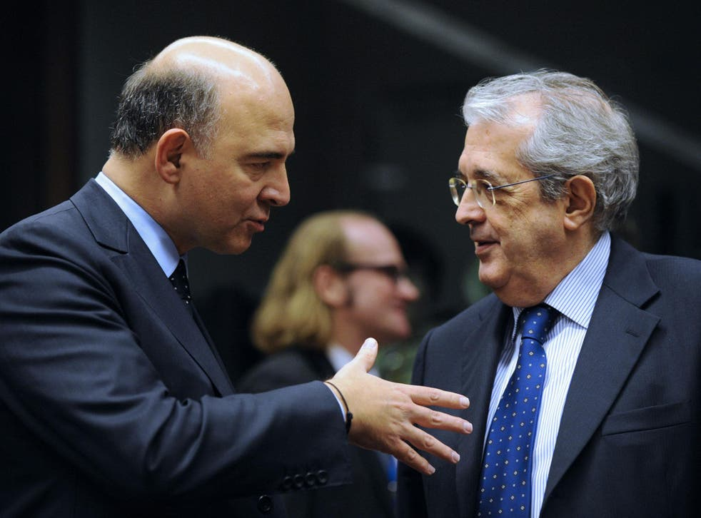 French Economy, Finance and Foreign Trade Minister, Pierre Moscovici (L) speaks with Italian Minister of Economy and Finance Fabrizio Saccomanni prior to a Eurozone finance ministers meeting at the EU Headquarters in Brussels on November 14
