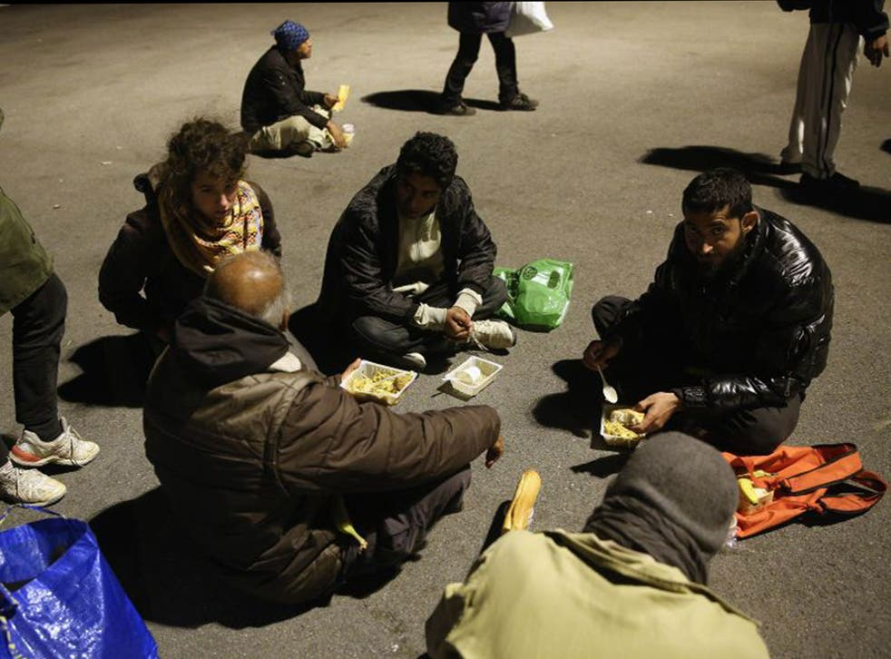 Migrants eat their evening meal at a centre run by volunteers in Calais. France has pledged to take 500 Syrian refugees