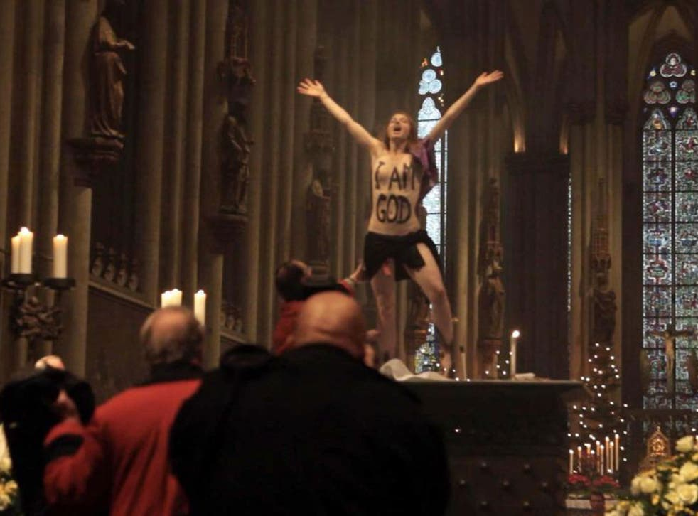 A topless Femen activist with the words 'I am God' painted on her chest stands on the altar during the Christmas Day service in Cologne Cathedral