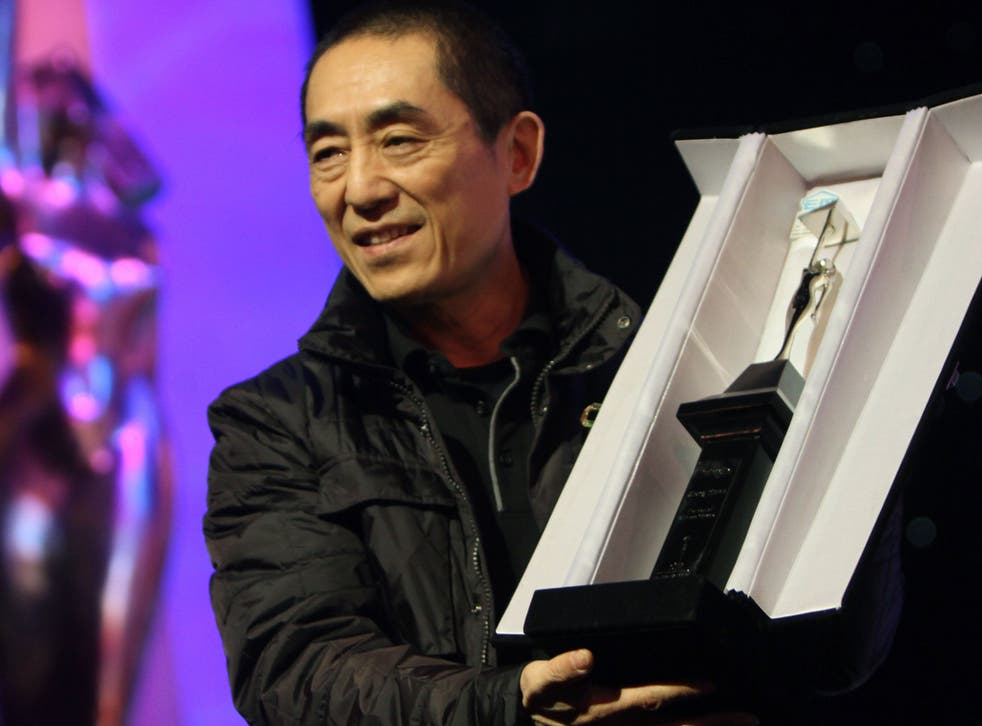 Chinese director Zhang Yimou receives a lifetime achievement award during the closing ceremony of the 35th Cairo International Film Festival