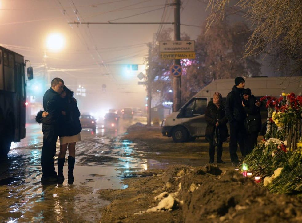 Russian people grieve at the site of the second terrorist explosion, which happened on a trolleybus, at a street in Volgograd