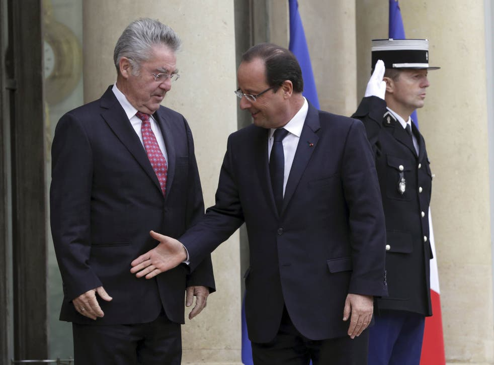 Awkward positioning: Francois Hollande goes for a handshake with Austrian President Heinz Fischer but misses the target