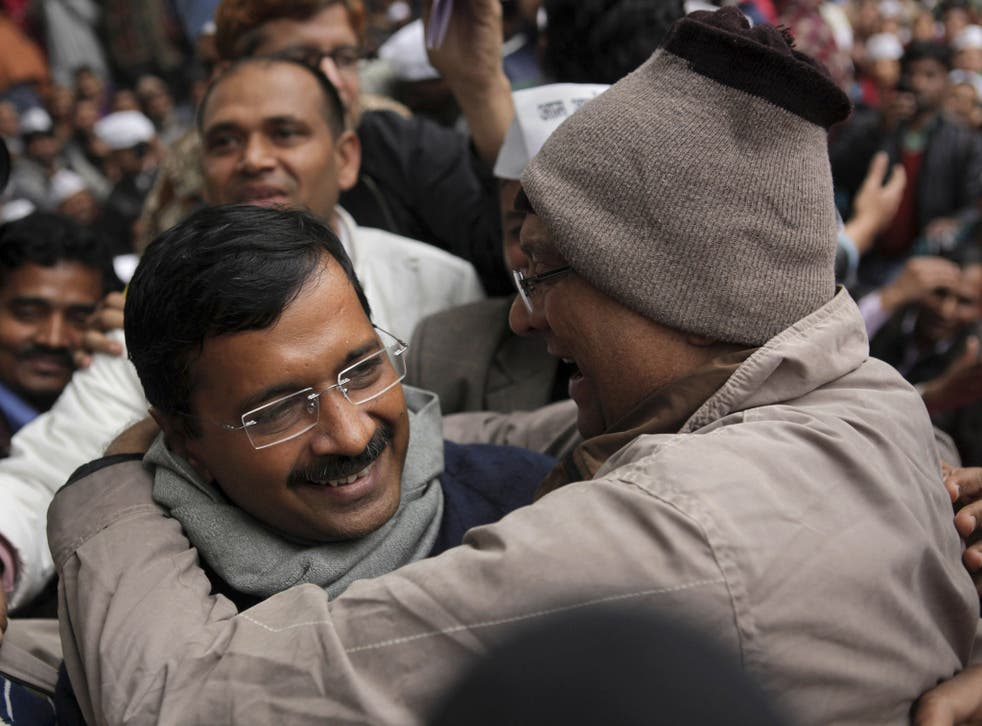 A supporter of Aam Aadmi Party, or Common Man's Party, greets its leader Arvind Kejriwal, left, a former tax official, on his arrival at a public meeting in New Delhi on Sunday