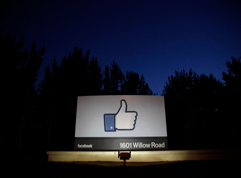 The sun rises behind the entrance sign to Facebook headquarters in Menlo Park.