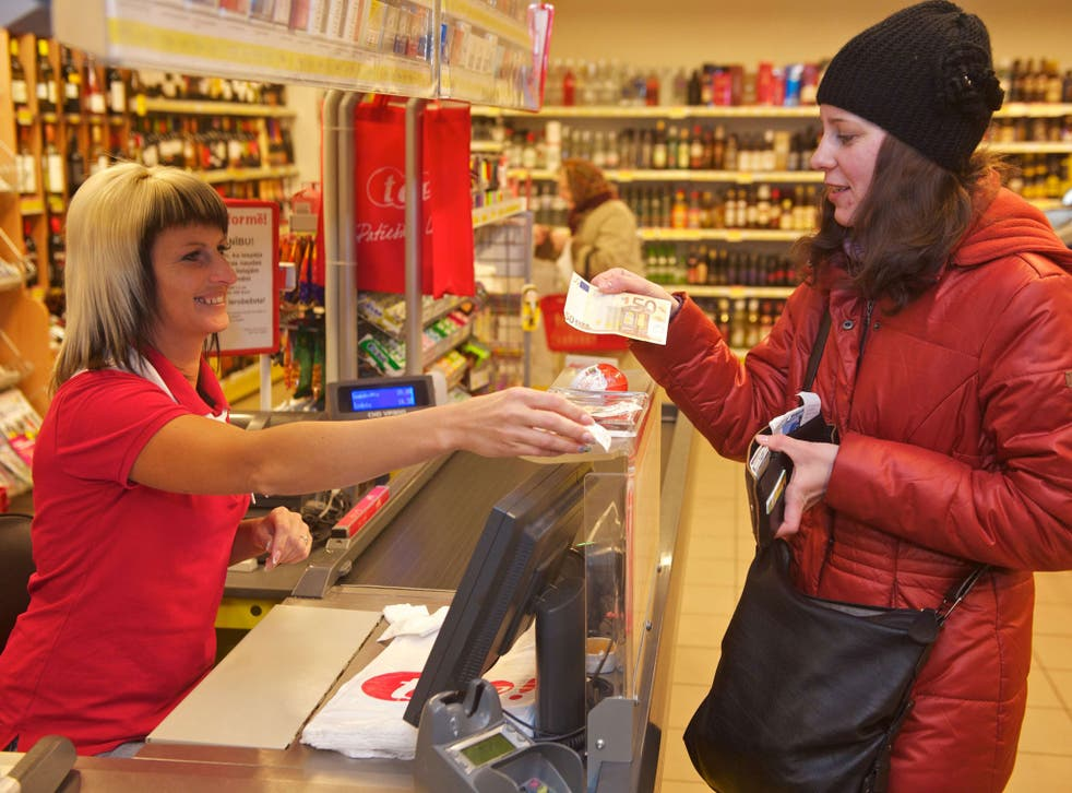 A woman pays for her shopping in euros at a supermarket in Rujiena, near the border with Estonia. On 1 January Latvia became the 18th country to adopt the Euro