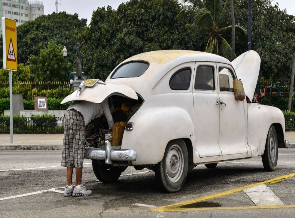 A Cuban attempts to repair his old car in Havana on the day the free sale of cars in Cuba was officially authorized.