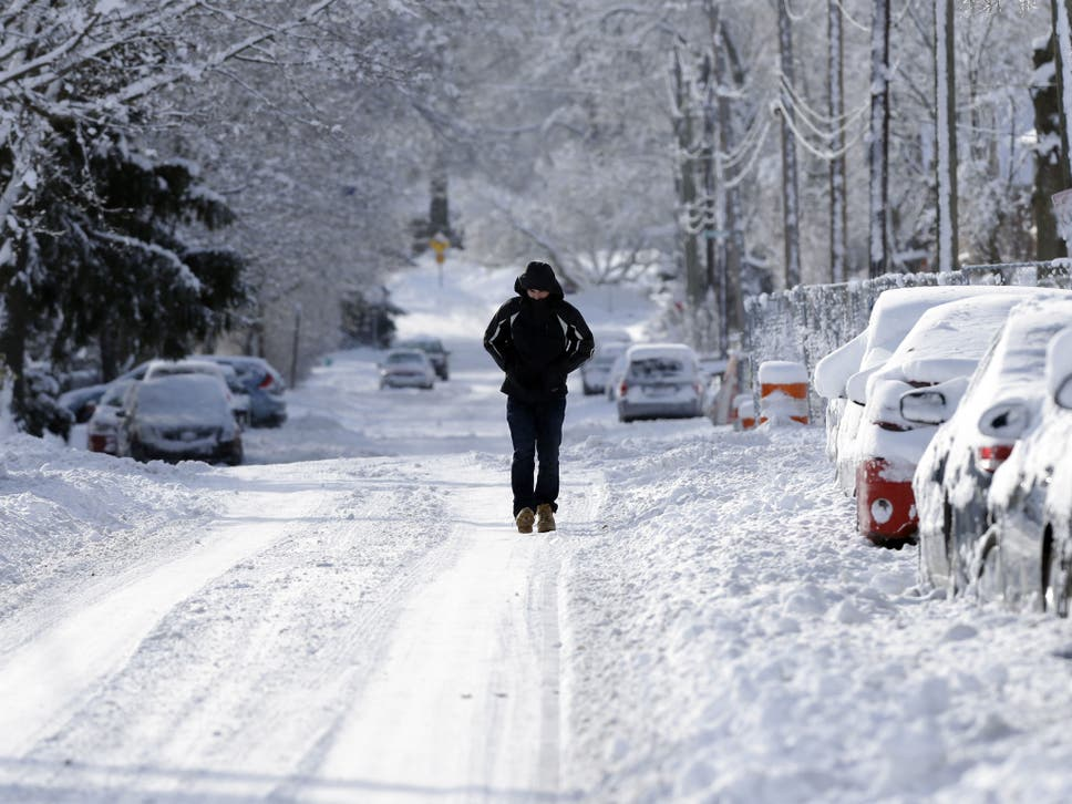 A pedestrian makes their way along a snow packed street in Indianapolis & What is a polar vortex? The arctic winds that brought cold air and ...