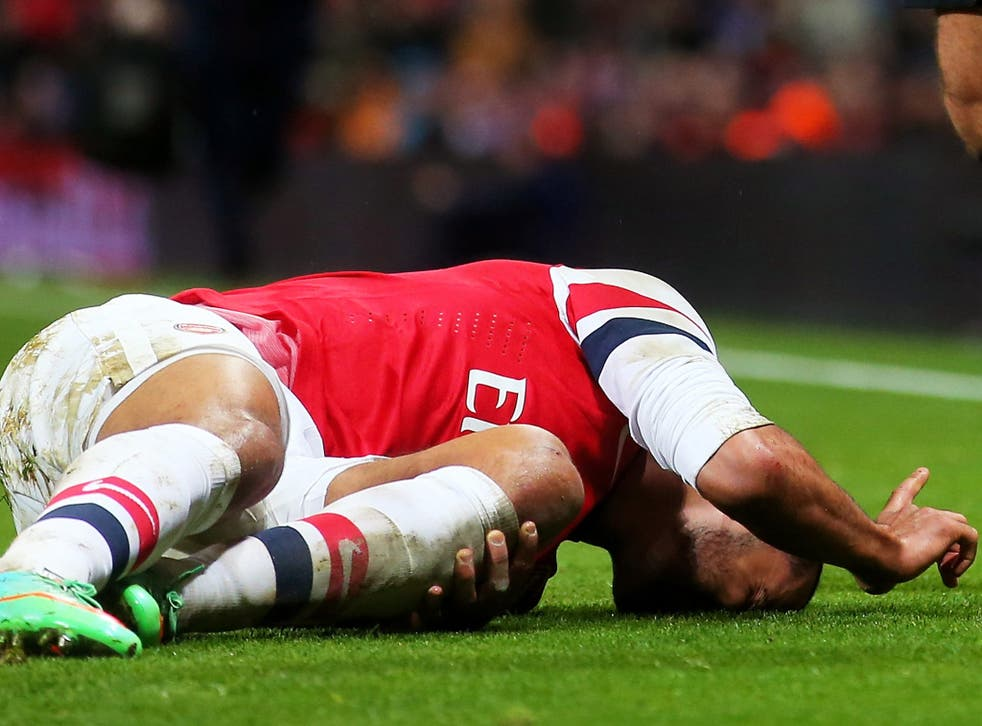 Theo Walcott lies injured on the pitch in Arsenal's FA Cup victory over Tottenham