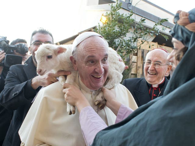 The pope has a lamb put around his neck by a woman dressed as a character from the nativity scene at Church of St Alfonso Maria dei Liguori in the outskirts of Rome