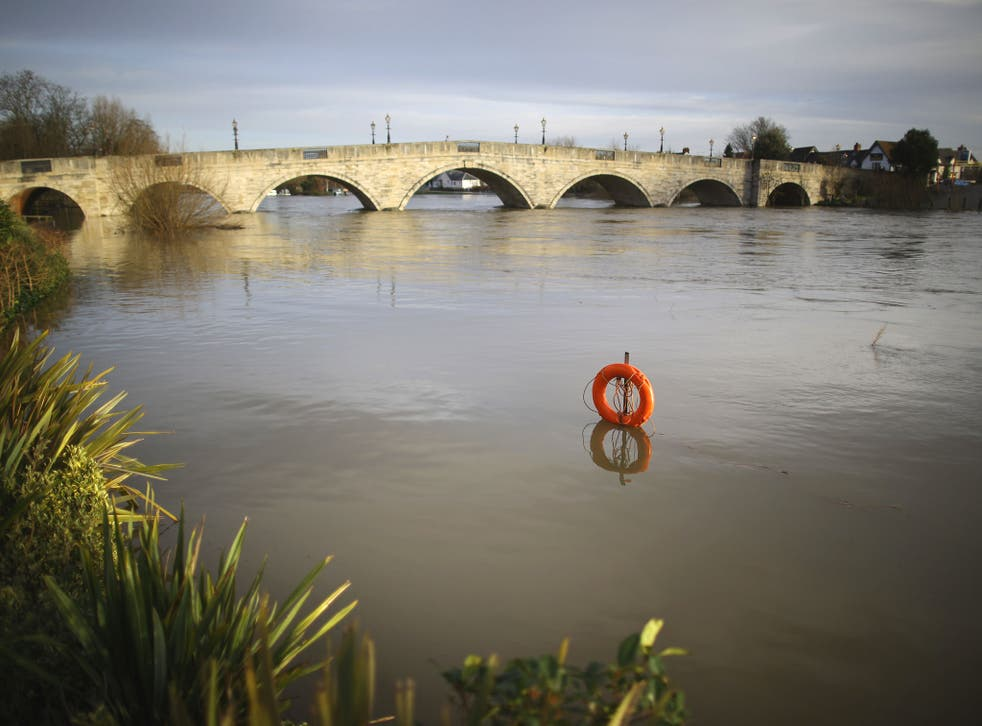 A lifebelt is almost submerged after the River Thames flooded in Chersey