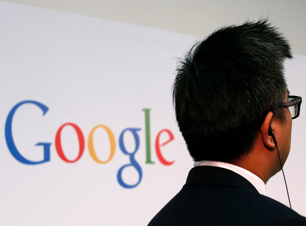 A man stands in front of a Google logo.