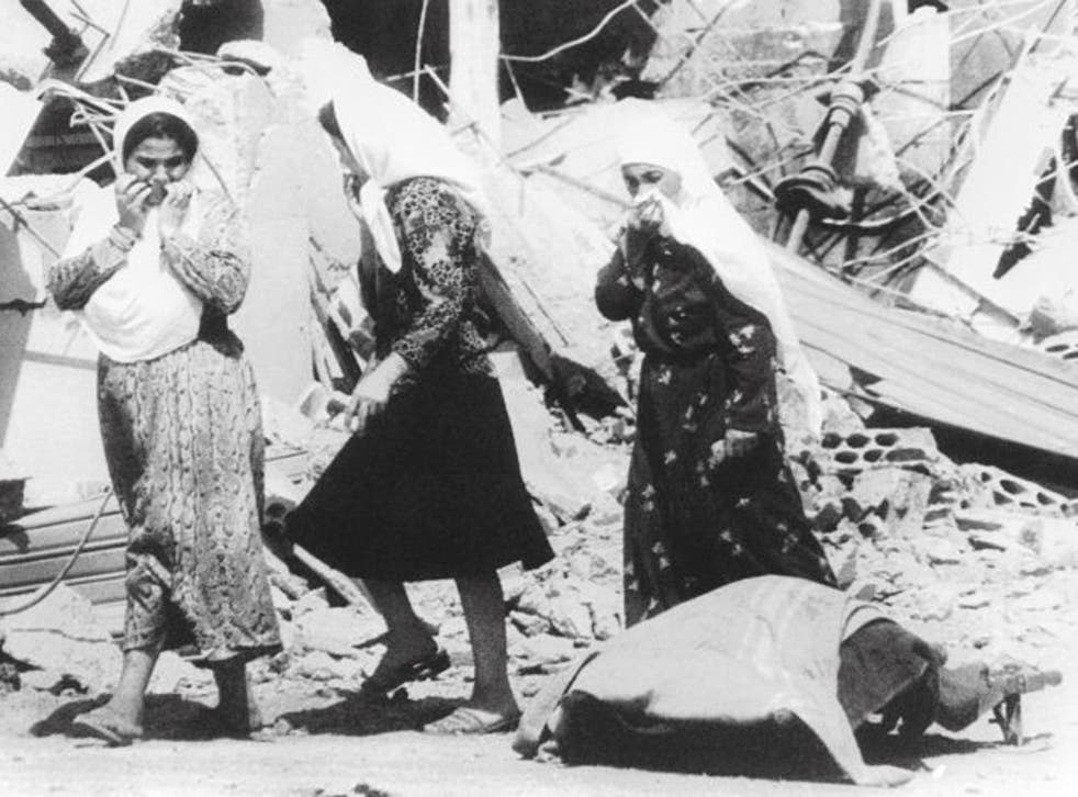 Palestinian women pass the body of one of the victims of the massacres in the Palestinian refugee camp of Sabra