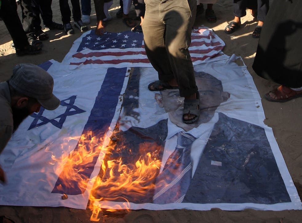 Palestinian Salafists walk on top of a picture of US President Barack Obama while burning Israeli and US flags during a protest against an amateur film mocking Islam in Rafah in the southern Gaza Strip on September 14, 2012