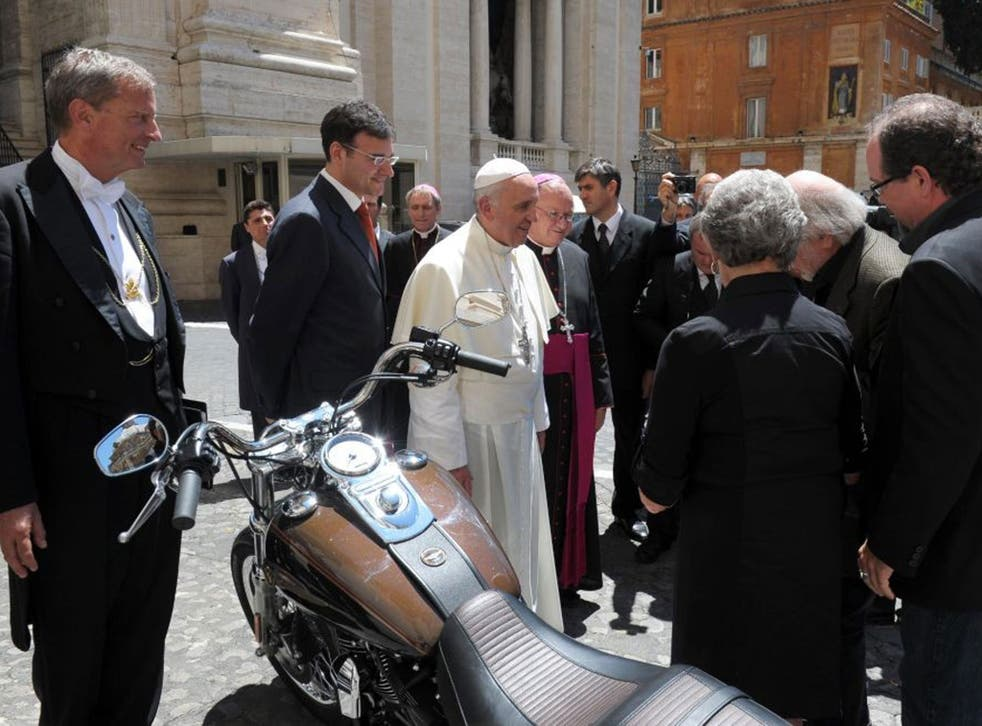 Pope Francis being presented with a Harley Davidson motorcycle in the Vatican last year.